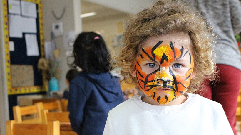 girl with cat face paint at daycare