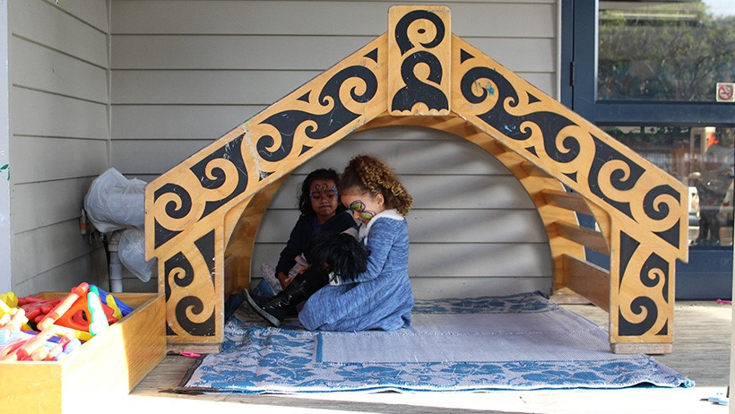 children playing in marae playhouse at daycare