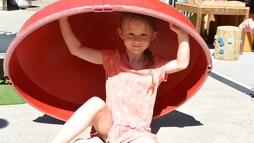 girl playing under big container at daycare