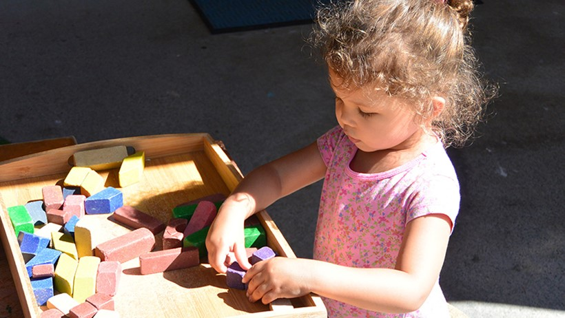 girl playing with blocks at daycare