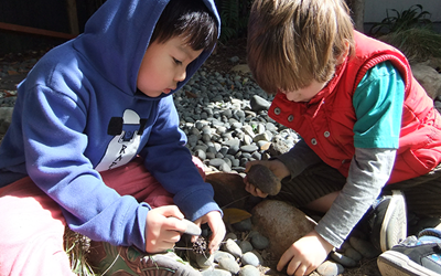 boys exploring stones and wood at daycare