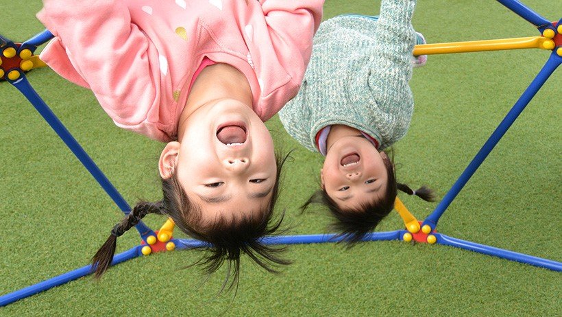 girls hanging upside down from bars at daycare