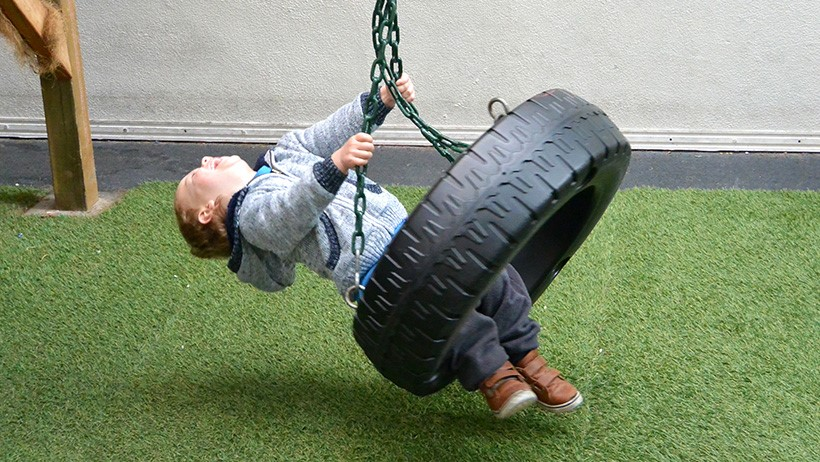 boy laughing swinging on tyre swing at daycare