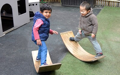 boys balancing on curved wood at daycare
