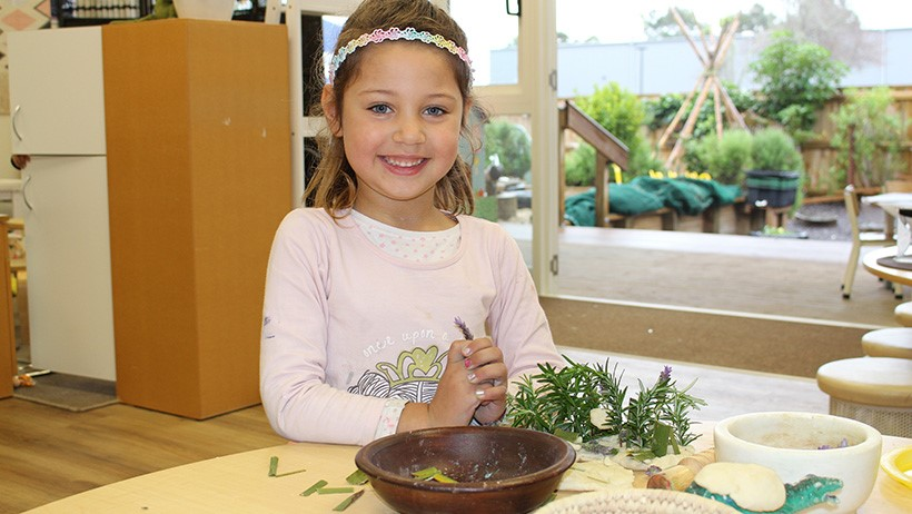 girl playing with plant mixture at daycare
