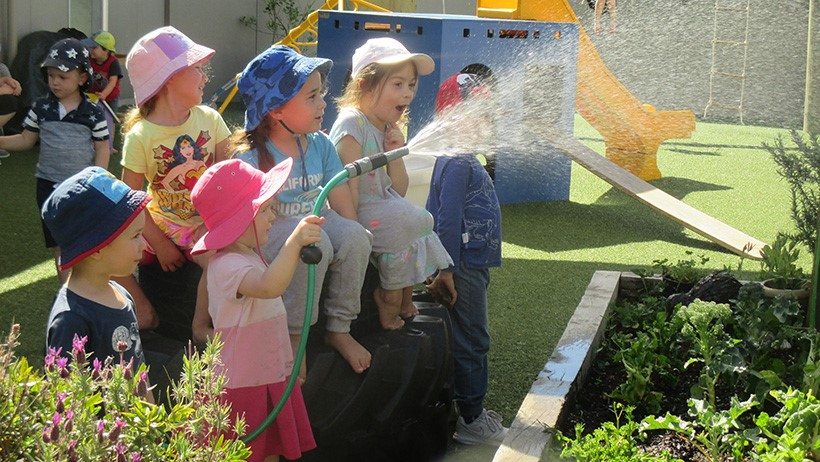 children watering plants with hose at daycare