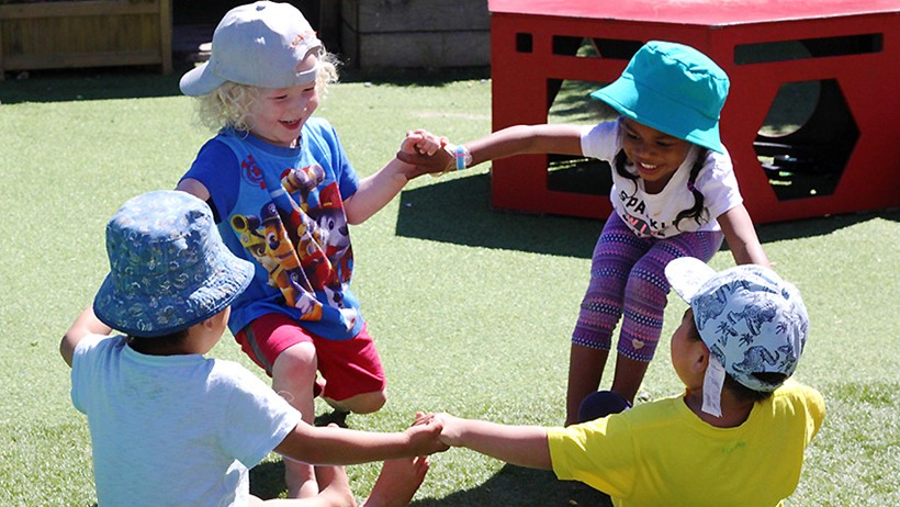 children hold hands in circle at daycare